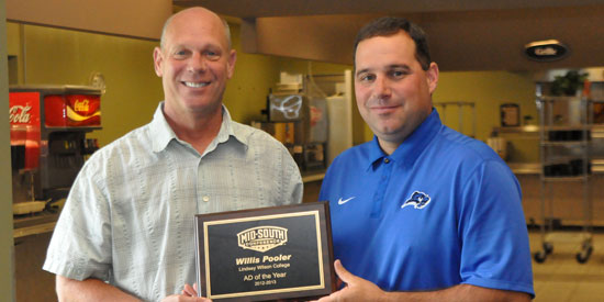 Mid-South Commissioner Steve Baker (left) presents Willis Pooler with the conference's athletic director of the year award.