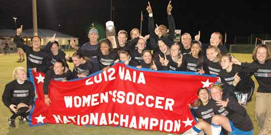 Lindsey Wilson holds up the 2012 NAIA Women's Soccer National Champion banner in Orange Beach, Ala.